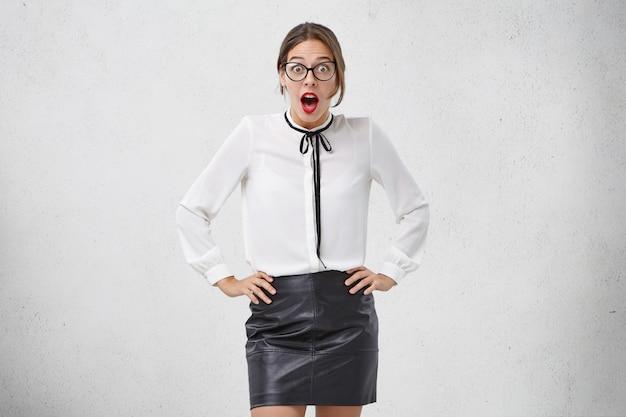 アイウェア、ブラウス、スカートの恐ろしい驚きのエレガントな女性が腰に手を保つ 無料写真