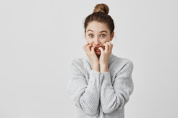 Волосы ужаса женщины нося в topknot смотря испуганный кусать ее ногти в стрессе. женский менеджер по продажам в беде, выражая негативные эмоции. концепция ужаса и страха Бесплатные Фотографии