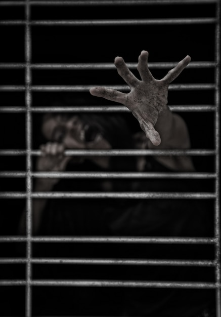 Horror scene of a possessed woman ghost halloween in dark cage pound room Premium Photo