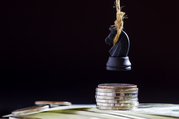 Horse or king of chess execute by hanging on dollar banknote and coin in darkness background. Premium Photo