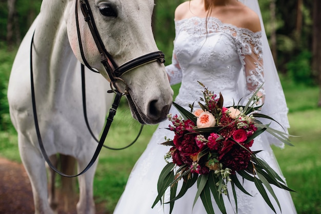 Horse sniffing a bouquet of flowers in the hands of the bride Premium Photo
