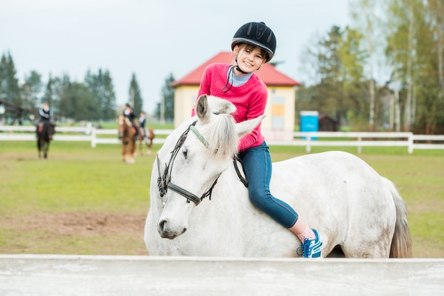 Horseback riding, lovely equestrian - little girl is riding a horse Premium Photo