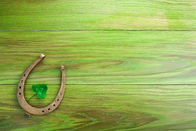 호스 슈와 클로버 녹색 나무 배경입니다. 녹색 네 잎 클로버. 성 패트릭의 날 상징. 프리미엄 사진
