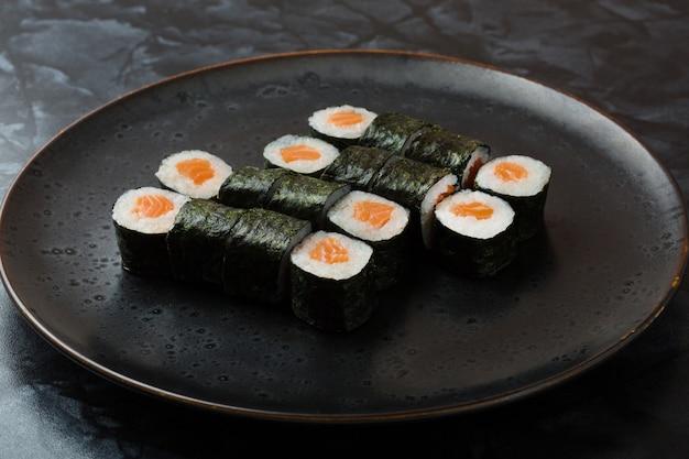 Hosomaki свертывает крупный план на черной плите с селективным фокусом. роллы с морскими водорослями, рисом, лососем Premium Фотографии