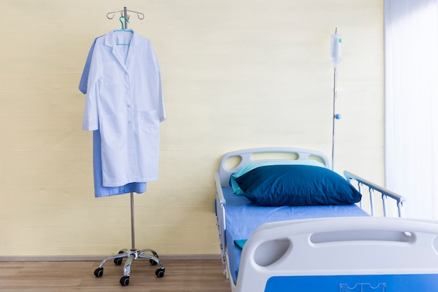 Hospital room with empty bed, infusion set, intravenous fluid and doctor suite. Premium Photo