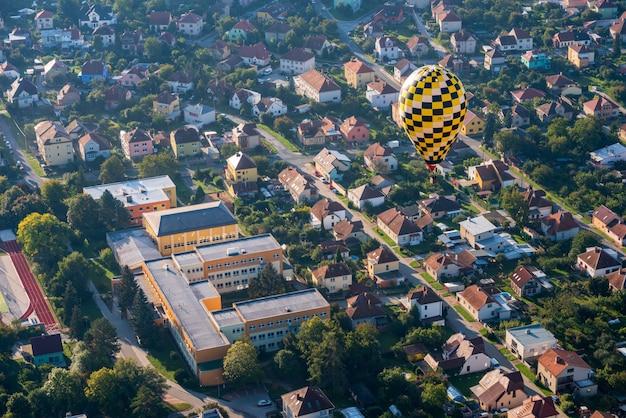 小さなチェコの都市の上空を飛行する熱気球 無料写真