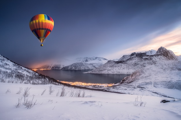 Hot air balloon flying on snow hill with fordgard town in winter Premium Photo