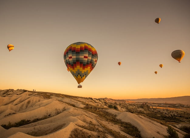 Hot air balloons over the hills and the fields during sunset in cappadocia, turkey Free Photo