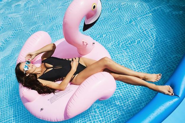 ホットでファッショナブルなブルネット、スタイリッシュな黒のビキニと魅力的なサングラスで完璧なセクシーなボディを持つフィットネスモデルの女性、膨脹可能なピンクのフラミンゴで日焼けして、スイミングプールでポーズ Premium写真