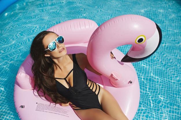 スイミングプールでフローティングピンクのフラミンゴで日焼けするスタイリッシュで黒いビキニと魅力的なサングラスで完璧なセクシーなボディを持つホットでファッショナブルなブルネットモデルの女性 Premium写真