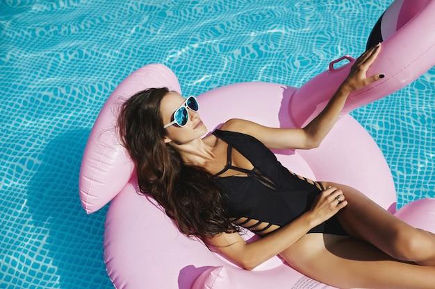 スイミングプールでポーズをとって浮かぶピンクのフラミンゴで日焼けするスタイリッシュで黒いビキニと魅力的なサングラスで完璧なセクシーなボディを持つホットでファッショナブルなブルネットモデルの女性 Premium写真