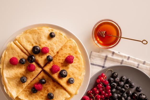 新鮮な熟したベリー、赤スグリ、ブラックベリーを皿に、小さなガラスのボウルに蜂蜜をテーブルに載せた、食欲をそそる自家製パンケーキ Premium写真