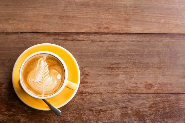 Hot art latte coffee in a cup on wooden table. Free Photo