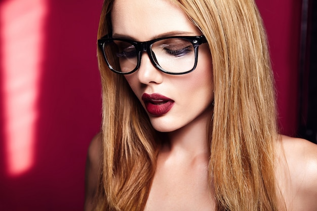 Hot beautiful blond woman model with fresh daily makeup with dark lips color and clean healthy skin on red background in glasses Free Photo