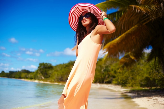 Hot beautiful woman in colorful sunhat and dress walking near beach ocean on hot summer day near palm Free Photo