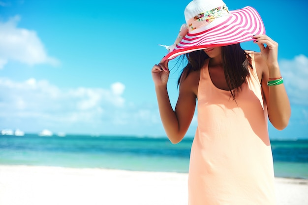 Hot beautiful woman in colorful sunhat and dress walking near beach ocean on hot summer day on white sand Free Photo