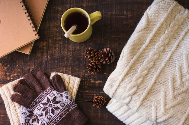 Hot beverage and cones near notebook and knitted clothes Free Photo
