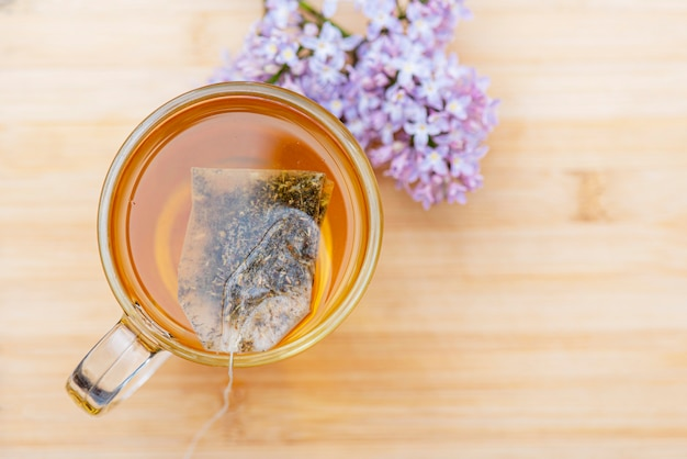 Hot beverage in glass mug on wooden table. close-up herbal tea in bag tea, top view Premium Photo