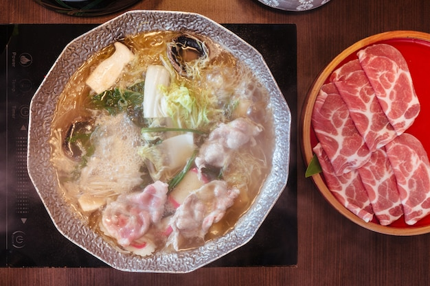Hot and boiling shabu broth with cabbage, eryngii, enotitake, tofu and kurobuta pork inside hot pot. Premium Photo