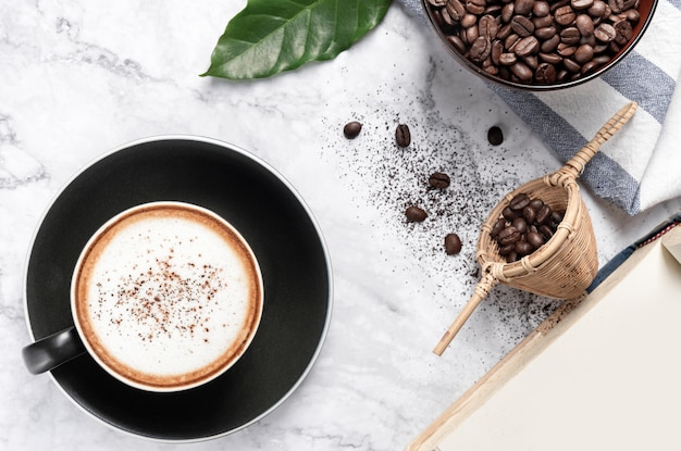 Hot cappuccino coffee with coffee beans the ground on marble table Premium Photo