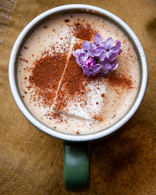 Hot cappuccino coffee with flower petals in a cup on piece of sack Free Photo