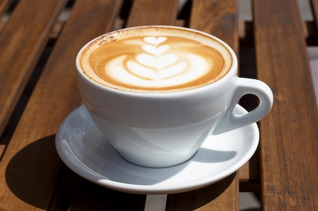 Hot cappuccino with froth and pattern on wooden background, side view Premium Photo