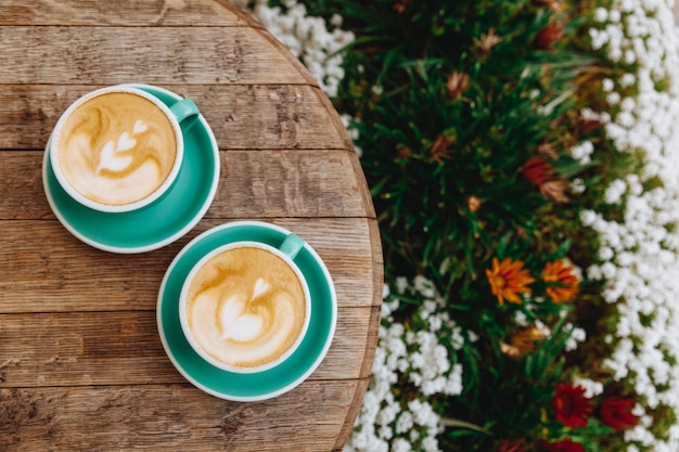 Hot cappuccino with latte art on wooden table of terrace Premium Photo