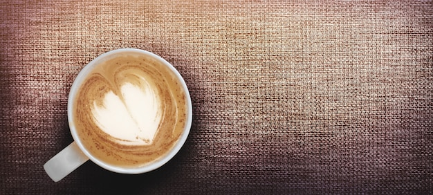 コーヒーカップの遅いハートアートの形のホットカプシンノコーヒーは、バナーサイズの茶色の籐で提供しています Premium写真