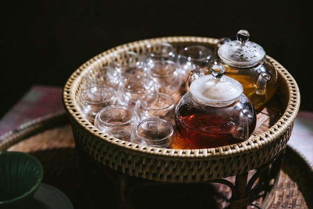 Hot chamomile tea in glass tea pot with empty glasses in basket for testers. Premium Photo