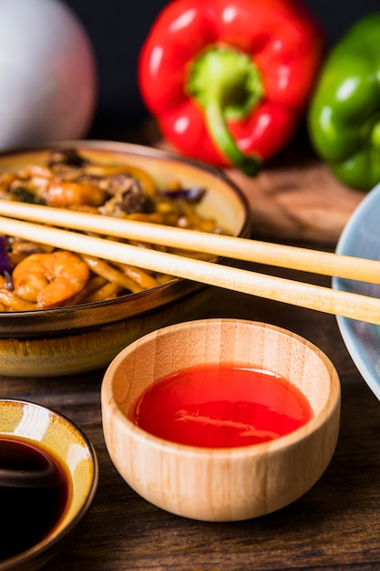 Hot chili sauce in wooden bowl with udon noodles with shrimp on wooden table Free Photo