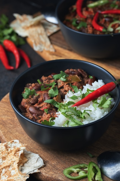Hot chilli con carne with minced beef, vegetables, rice. topped with chilli pepper. mexican food tasty and spicy. Premium Photo