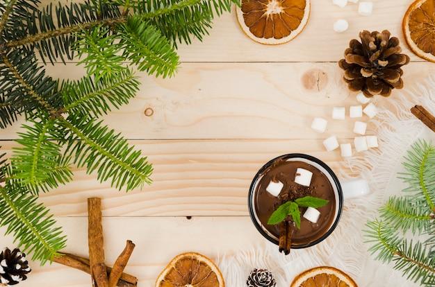 Cioccolata calda sulla scrivania con marshmallow, arance e dossi di abete Foto Gratuite