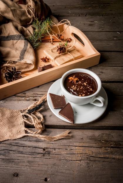 ホットチョコレートマグと素朴なテーブルにクリスマスプレゼント Premium写真