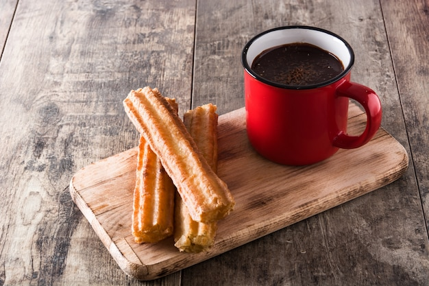 Hot chocolate with churros on wooden table Premium Photo