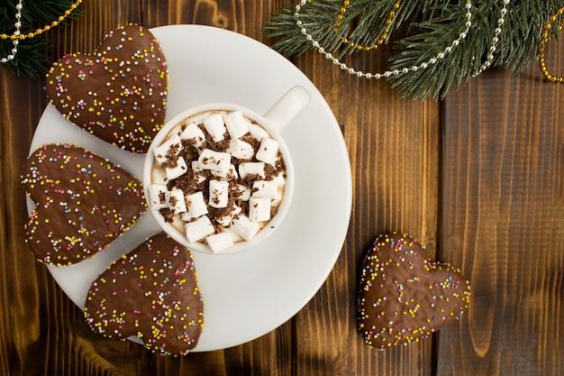 白いカップにマシュマロと茶色の木製の背景にクリスマスの組成物とホットチョコレート。コピースペース。上面図。 Premium写真