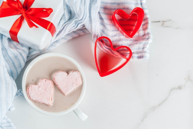 Hot chocolate with marshmallows in the shape of hearts, valentine's day celebration, with red cookie cutters and valentine's gift box Premium Photo
