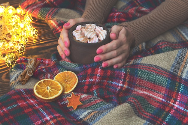 Hot cocoa with marshmallow in hand girl in knitted sweater, blanket and dry oranges with christmas lights. christmas, winter, new year concept. copy space, Premium Photo