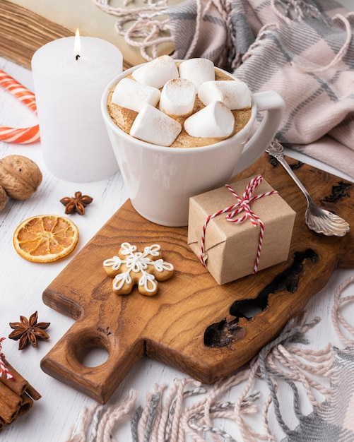 Hot cocoa with marshmallows in cup with present and candle Free Photo
