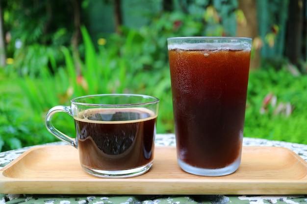 Горячий кофе и кофе со льдом на деревянном подносе, поданные на садовом столе Premium Фотографии