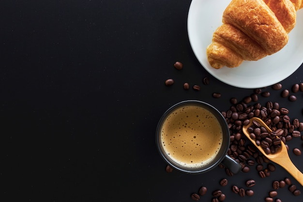 Hot coffee, bean and butter croissants on black table Premium Photo