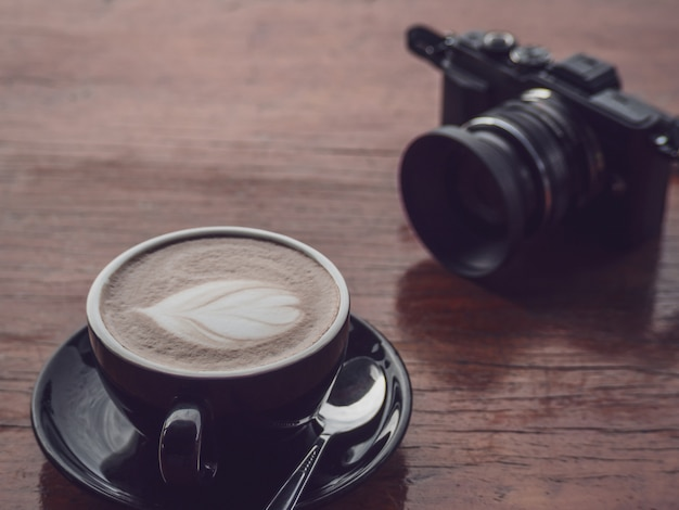 Hot coffee in black cup with camera Premium Photo