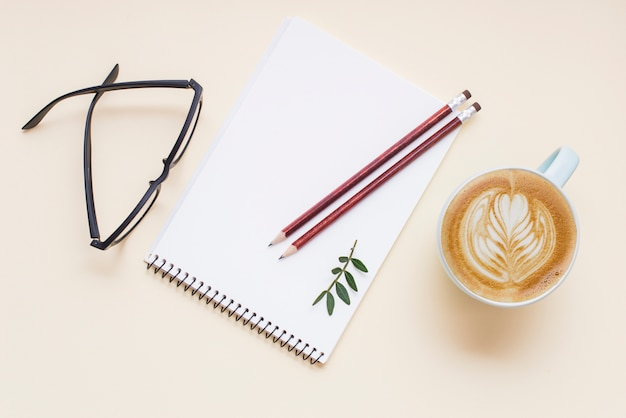 Hot coffee cappuccino latte art; eyeglasses and pencils on white spiral notepad Free Photo