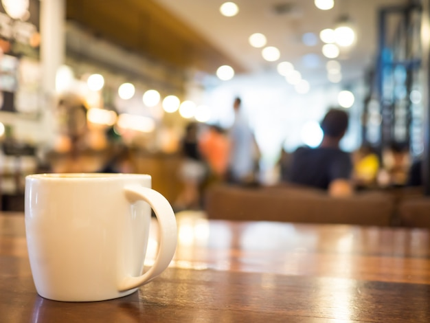 Hot coffee cappuccino in white cup on wooden table and blurred background cafe stores. Premium Photo