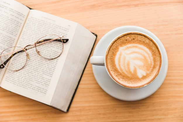 Hot coffee cup with cappuccino latte art and eyeglasses over an open book on table Free Photo