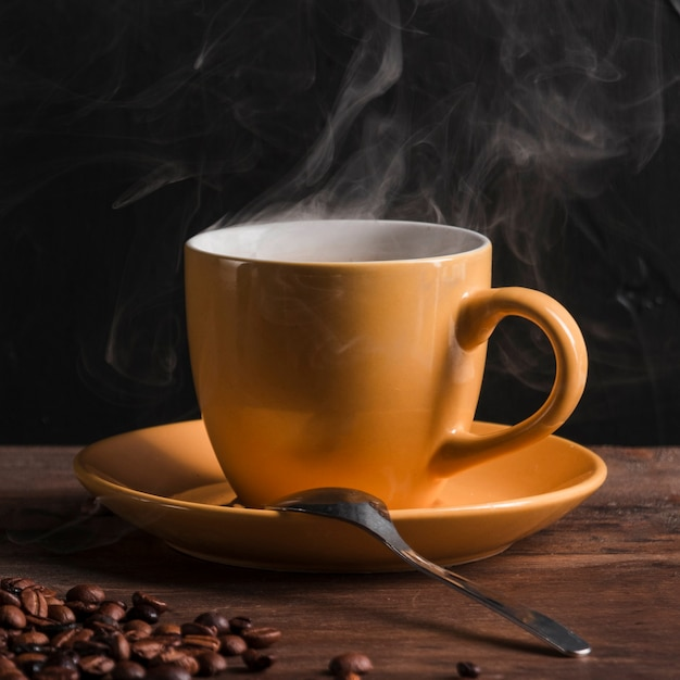Hot coffee in cup with spoon on plate Free Photo