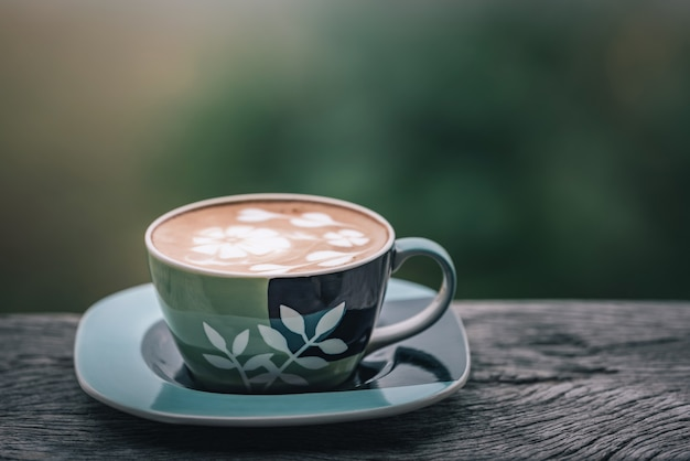 Hot coffee glass cup on wooden table in coffee shop with green natural background. Premium Photo