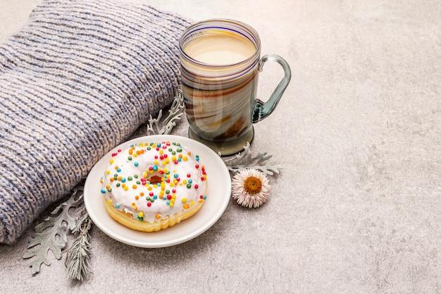 ドーナツとホットコーヒー。セーター、葉、花で気分を良くする冬の飲み物。 Premium写真