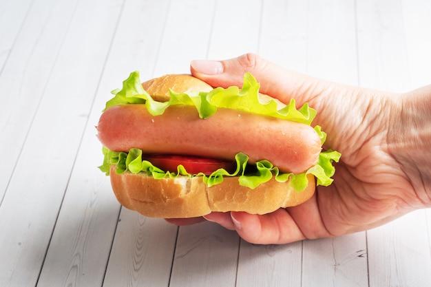 Хот-дог с салатом помидор и колбаса держать в руках. Premium Фотографии