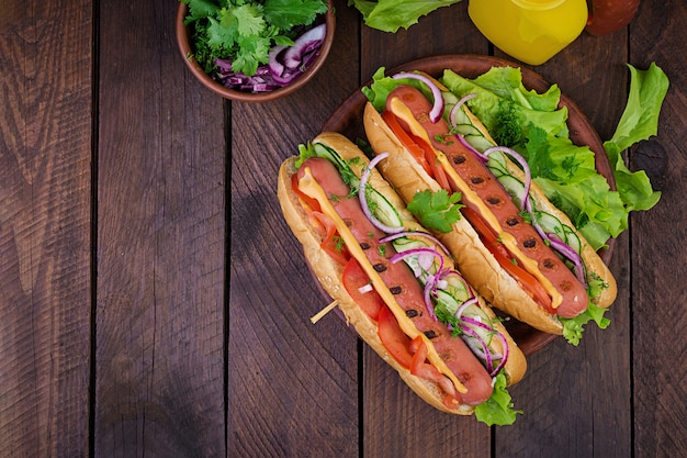 Хот-дог с колбасой, огурцом, помидорами и листьями салата на темный деревянный стол. летний хот-дог. вид сверху Бесплатные Фотографии