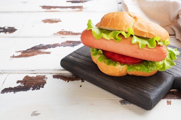 Хот-доги на деревянной доске. хот-дог с листьями салата помидор и колбаса. копировать пространство Premium Фотографии